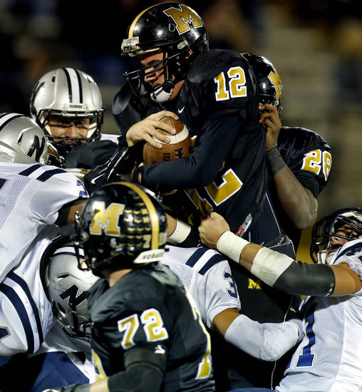 Midwest City quarterback Brendan Brown goes up and over on a fourth and one to gain the necessary yard against Edmond North in high school football on Friday, Nov. 1, 2013 in Midwest City, Okla.  Photo by Steve Sisney, The Oklahoman