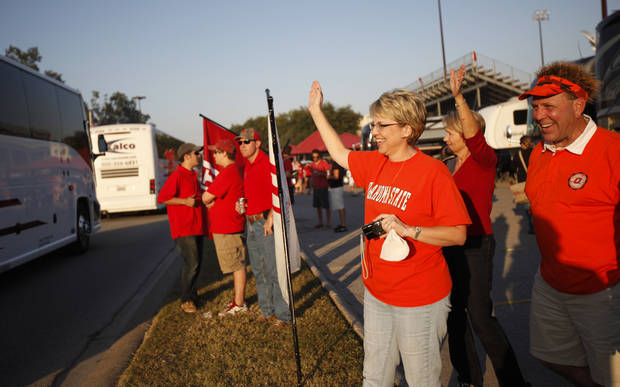 Tracie and Steve Stands of Edmond, Okla., wave to the OSU team bus before the football game between the University of Louisiana-Lafayette and Oklahoma State University at Cajun Field in Lafayette, La., Friday, October 8, 2010. Photo by Bryan Terry, The Oklahoman