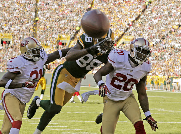 San Francisco 49ers&#039; Donte Whitner (31) and  Perrish Cox (20) break up a pass intended for Green Bay Packers&#039; Jermichael Finley (88) during the first half of an NFL football game Sunday, Sept. 9, 2012, in Green Bay, Wis. (AP Photo/Jeffrey Phelps) ORG XMIT: WIMG126