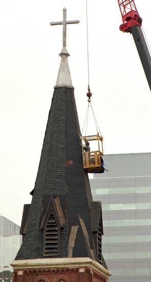 A worker puts shingles on the steeple of St. Joseph Old Cathedral in downtown Oklahoma City Tuesday morning. The church is undergoing extensive renovationafter being damaged in the Alfred Murrah Federal Building car bomb explosion on April 19.