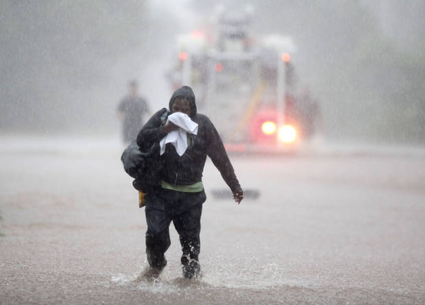 A motorist walks away from her stalled vehicle as Oklahoma City firefighters work to rescue other stalled vehicles on Hefner Road between Kelly Avenue and the Broadway Extension in Oklahoma City, OK, Monday, June 14, 2010. By Paul Hellstern, The Oklahoman