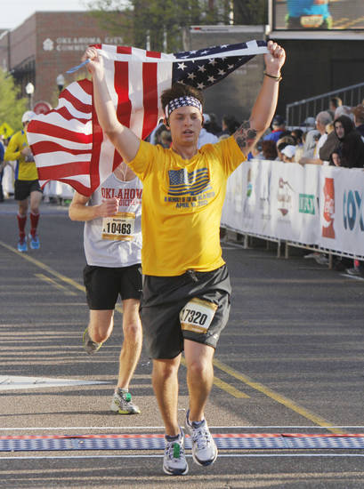 Desmond Greer waves an American flag as he crosses the half-marathon finish line of the Oklahoma City Memorial Marathon in Oklahoma City, Sunday, April 28, 2013,  By Paul Hellstern, The Oklahoman
