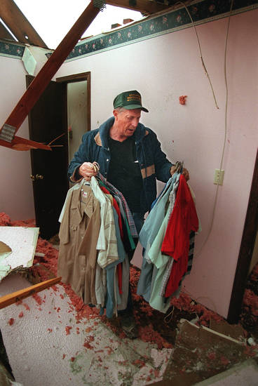 MAY 3, 1999 TORNADO: Tornado victims, damage: Jack Schafer carries clothes from damaged home in Muhall Oklahoma .