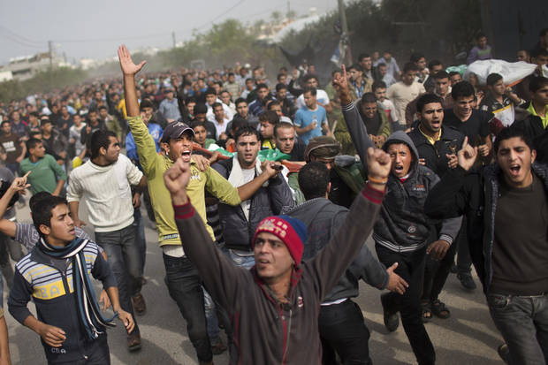 Palestinians chant slogans and carry the bodies of Hamas militants in Maghazi Refugee Camp, central Gaza Strip, Saturday, Nov. 17, 2012. According to local villagers, the militants were killed during an early morning Israeli airstrike. (AP Photo/Bernat Armangue)