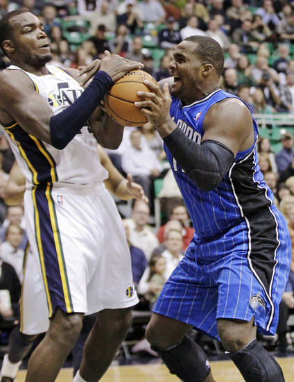 Orlando Magic power forward Glen Davis, right, and Utah Jazz power forward Paul Millsap (24) battle for a loose ball in the second quarter of an NBA basketball game, Wednesday, Dec. 5, 2012, in Salt Lake City. (AP Photo/Rick Bowmer)