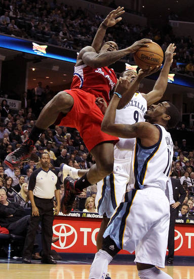 Los Angeles Clippers guard Eric Bledsoe (12) gets fouled by Memphis Grizzlies guard Tony Allen (9) while going to the basket against Grizzlies guard Mike Conley (11) in the first half of an NBA basketball game on Monday, Jan. 14, 2013, in Memphis, Tenn. (AP Photo/Lance Murphey)