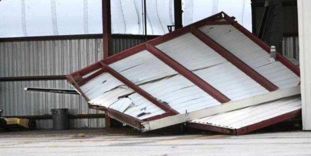 A hangar door rests on an airplane at Max Westheimer Airport in Norman Tuesday after severe weather moved through the state Monday night. <strong>STEVE SISNEY - THE OKLAHOMAN</strong>