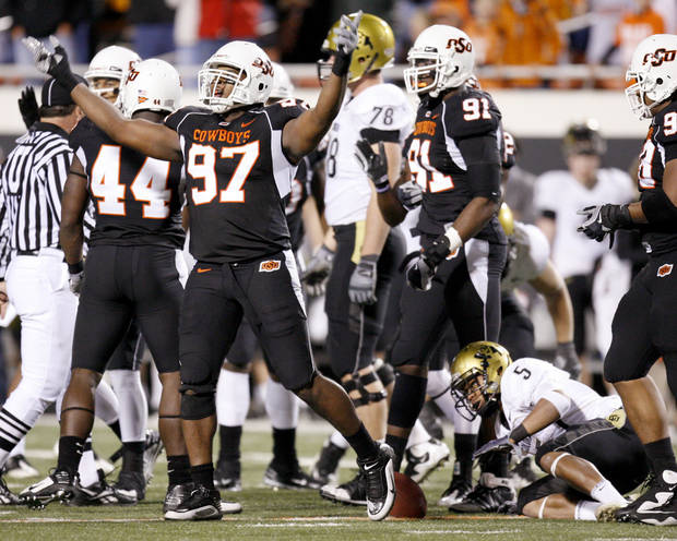 OSU&#039;s Jermiah Price celebrates as Colorado&#039;s Rodney Stewart gets up during the college football game between Oklahoma State University (OSU) and the University of Colorado (CU) at Boone Pickens Stadium in Stillwater, Okla., Thursday, Nov. 19, 2009. Photo by Bryan Terry, The Oklahoman