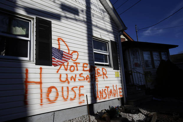 Homes severely damaged by Superstorm Sandy bear warnings on Staten Island in New York, Thursday, Jan. 10, 2013. The November storm damaged or destroyed 305,000 housing units in New York and more than 265,000 businesses were disrupted in the state.   (AP Photo/Seth Wenig)
