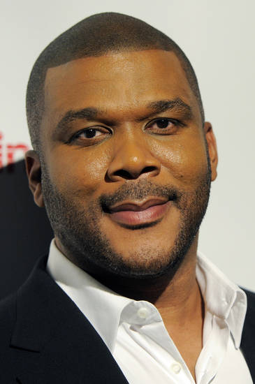 FILE - In this March 31, 2011 file photo, Tyler Perry, recipient of the CinemaCon Visionary Award, arrives for the CinemaCon Big Screen Achievement Awards in Las Vegas. Perry delivered on a Christmas promise when he handed the keys of a new four-bedroom house to an 88-year-old woman who lost her rural Georgia home to a fire. (AP Photo/Chris Pizzello, File) ORG XMIT: NY121