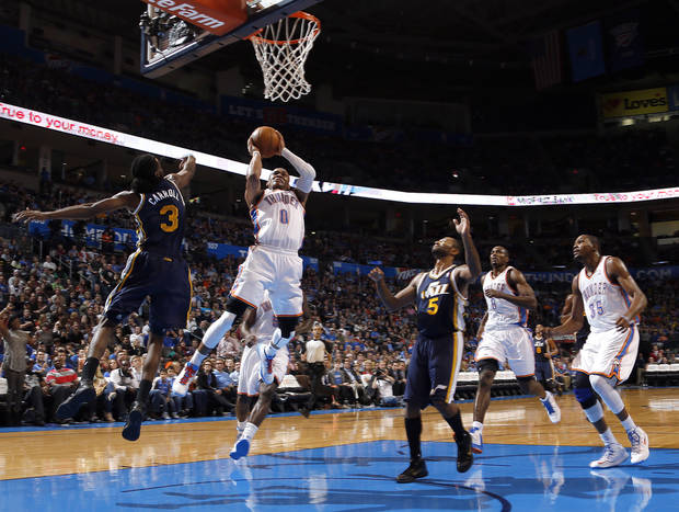 Oklahoma City's Russell Westbrook (0) shoots in between Utah's DeMarre Carroll (3) and Mo Williams (5) during the NBA game between the Oklahoma City and the Utah Jazz and the Chesapeake Energy Arena, Friday,Nov. 30, 2012. Photo by Sarah Phipps, The Oklahoman