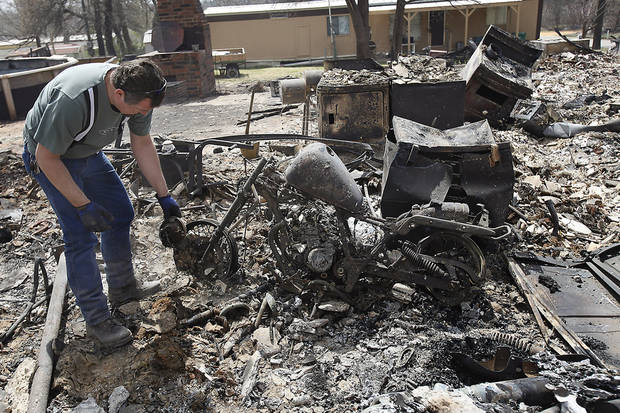 George West looks for anything left to a motorcycle that might be salvageable in the remains of a house that was destroyed by wildfires on Friday, April 10, 2009, in Choctaw, Okla.  Photo by Chris Landsberger, The Oklahoman