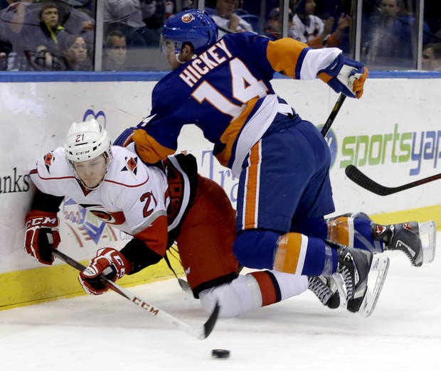 New York Islanders defenseman Thomas Hickey (14) checks Carolina Hurricanes left wing Drayson Bowman (21) against the boards in the first period of their NHL hockey game at Nassau Coliseum in Uniondale, N.Y., Sunday, Feb. 24, 2013. (AP Photo/Kathy Willens)