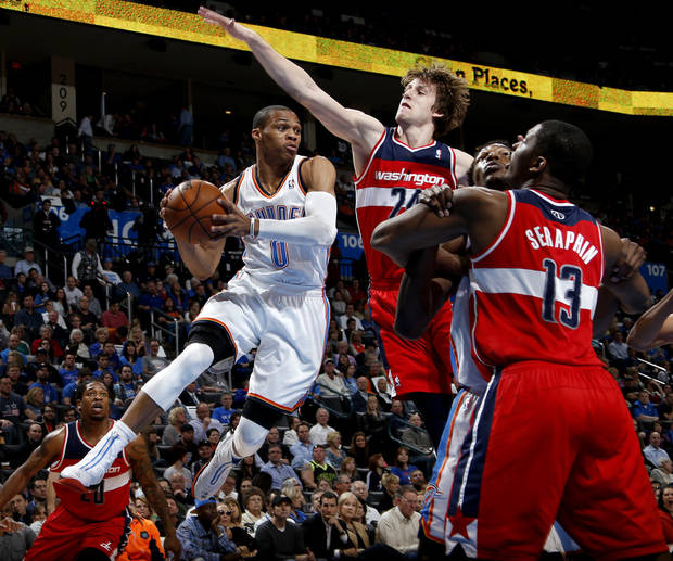Oklahoma City's Russell Westbrook (0) passes the ball beside Washington's Jan Vesely (24) during an NBA basketball game between the Oklahoma City Thunder and the Washington Wizards at Chesapeake Energy Arena in Oklahoma City, Wednesday, March 19, 2013. Photo by Bryan Terry, The Oklahoman