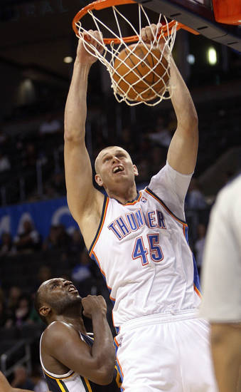 Oklahoma City Thunder center Cole Aldrich, right, dunks in front of Utah Jazz forward Al Jefferson, left, in the fourth quarter of an NBA basketball game in Oklahoma City, Sunday, Oct. 31, 2010. Utah won 120-99. (AP Photo/Sue Ogrocki) ORG XMIT: OKSO114