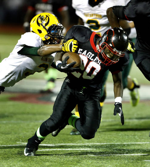 Del City's Carnez Brown carries as MacArthur's Barry Williams III tries to tackle him during a high school football game between the Lawton MacArthur Highlanders and the Del City Eagles on Friday, Sept. 27, 2013 in Del City, Okla. Photo by Steve Sisney, The Oklahoman