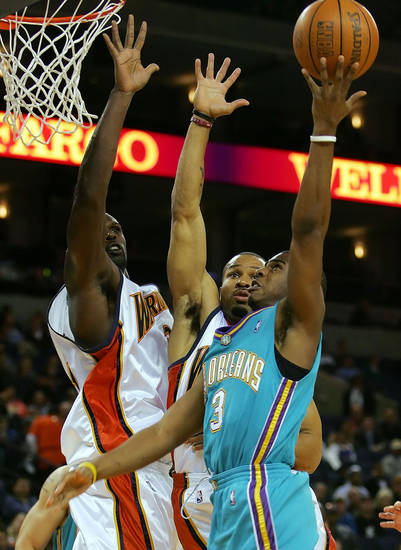New Orleans/Oklahoma City Hornets' Chris Paul, right, shoots past Golden State Warriors' Derek Fisher, middle,  and Adonal Foyle in the first half of an NBA basketball game in Oakland, Calif. on Wednesday, March 29, 2006. (AP Photo/Marcio Jose Sanchez)