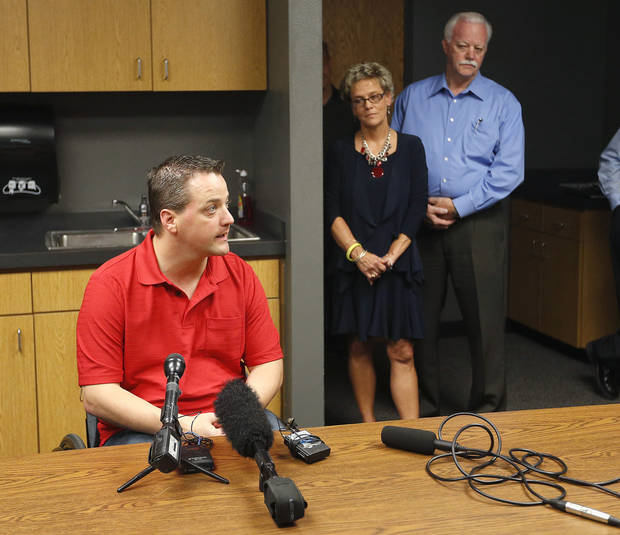 JAN PEERY / GREG PEERY: Oklahoma City Police Officer Chad Peery speaks to the media in Oklahoma City, Thursday, July 12, 2012, as his parents Jan and Greg look on. Photo by Sarah Phipps, The Oklahoman. ORG XMIT: OKOKL