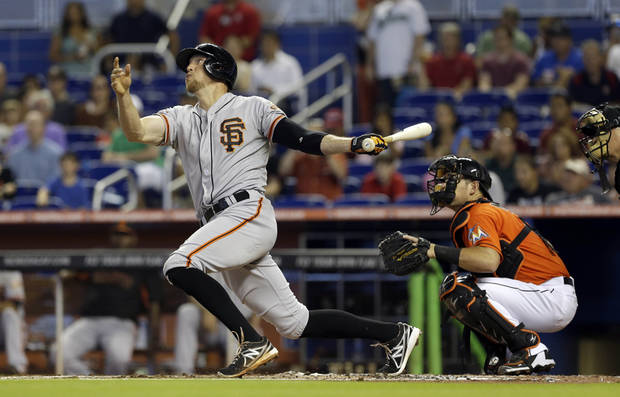 San Francisco Giants' Hunter Pence, left, follows through on his two-run home run against the Miami Marlins in the first inning of a baseball game on Sunday, Aug. 18, 2013, in Miami. Gregor Blanco scored on the home run. (AP Photo/Alan Diaz)