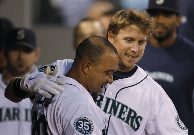 Seattle Mariners' Justin Smoak, right, is congratulated in the dugout by Miguel Olivo after hitting a solo home run on a pitch from Minnesota Twins' Scott Diamond during the eighth inning of a baseball game in Seattle on Saturday, Aug. 18, 2012. (AP Photo/John Froschauer)