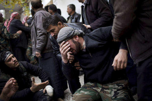 A Free Syrian Army fighter cries during the funeral of his comrade killed by the Syrian Army in Azaz, Syria, Thursday, Dec .13, 2012. (AP Photo/Manu Brabo) ORG XMIT: CAI118