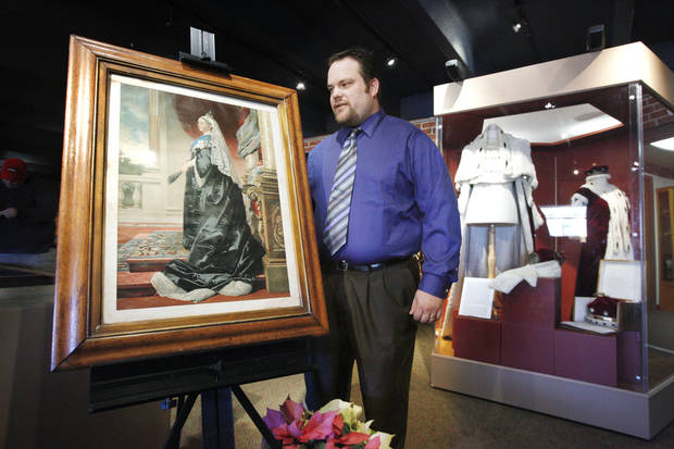 Museum director and curator Adam Lynn stands between a print from the 1800s of Queen Victoria and a display case with ceremonial robes belonging to the Burns family of Scotland on display at the Chisholm Trail Museum in Kingfisher. The exhibit has been extended to March 31. PHOTOS BY PAUL B. SOUTHERLAND, PAUL B. SOUTHERLAND