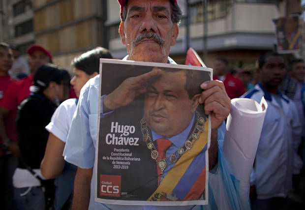 "A supporter of Venezuela's President Hugo Chavez poses for a picture while holding up a local newspaper featuring Chavez on the cover, at a rally in Caracas, Venezuela, Thursday, Jan. 10, 2013.  Hundreds of supporters gathered outside his presidential palace in an alternative inauguration, showing their support for the ailing leader and wearing T-shirts with the slogan ""I am Chavez.""  The government organized the rally for the cancer-stricken leader on the streets outside Miraflores Palace on what was supposed to be his inauguration day. A swearing-in ceremony has been indefinitely postponed, despite opposition complaints. (AP Photo/Ariana Cubillos)"