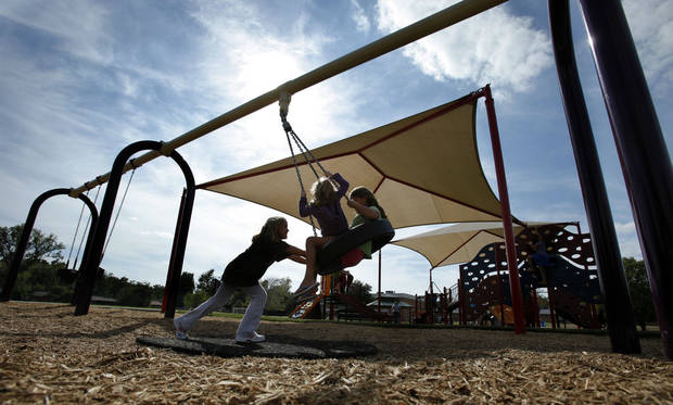 Children play on swings at a new neighborhood park adjacent to Monroe Elementary School.  PHOTOS BY STEVE SISNEY, THE OKLAHOMAN
