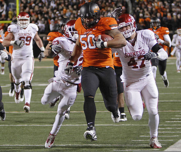 Oklahoma State's Jamie Blatnick (50) returns a fumble as he is chased by Oklahoma's Roy Finch (22) and Oklahoma's Trent Ratterree (47) during the Bedlam college football game between the Oklahoma State University Cowboys (OSU) and the University of Oklahoma Sooners (OU) at Boone Pickens Stadium in Stillwater, Okla., Saturday, Dec. 3, 2011. Photo by Chris Landsberger, The Oklahoman