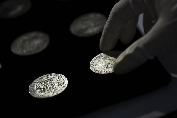 A worker of the ministry places silver coins from the shipwreck of a 1804 galleon, on its first display to the media at a ministry building, in Madrid, Friday, Nov. 30, 2012. Spanish cultural officials have allowed the first peep at 16 tons (14.5 metric tons) of the shipwreck, 'Nuestra Senora de las Mercedes' a treasure worth an estimated $500 million that a U.S. salvage company gave up after a five-year international ownership dispute. (AP Photo/Daniel Ochoa de Olza)