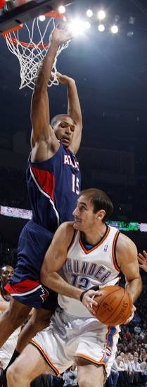 Nenad Krstic (12) of Oklahoma City works under the defense of Al Horford (15) of Atlanta during the NBA basketball game between the Atlanta Hawks and the Oklahoma City Thunder at the Ford Center in Oklahoma City, Tuesday, February 2, 2010. Photo by Nate Billings, The Oklahoman