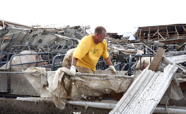 Wally Walters clears debris near animal pens at Farm 62 of Seaboard Foods near Hennessey, Okla., Saturday, May 24, 2008. The farm was severely damaged by a tornado. BY SARAH PHIPPS, THE OKLAHOMAN