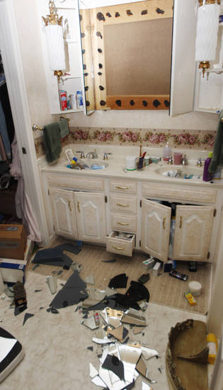 The mirror from a bathroom in the home of Joe and Mary Reneau lies in pieces on the floor in Sparks, Okla., Sunday, Nov. 6, 2011, following Saturday night's earthquake. (AP Photo/Sue Ogrocki) ORG XMIT: OKSO110
