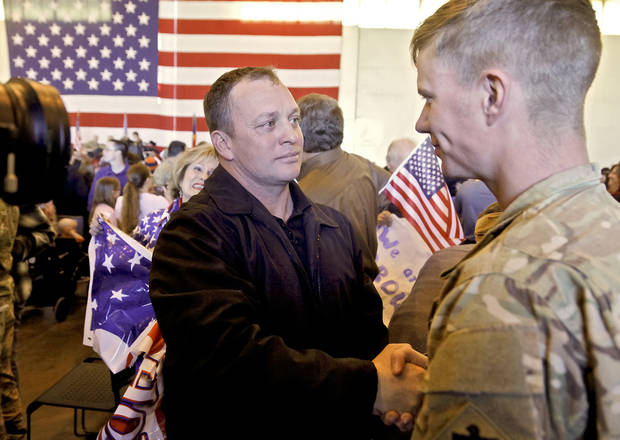 John Farrow shakes the hand of his son, Justin, to welcome him home during the return ceremony for more than 200 National Guard 45th Infantry Brigade Combat Team troops at the National Guard Base on Monday, March 12, 2012, in Oklahoma City, Oklahoma.  Photo by Chris Landsberger, The Oklahoman