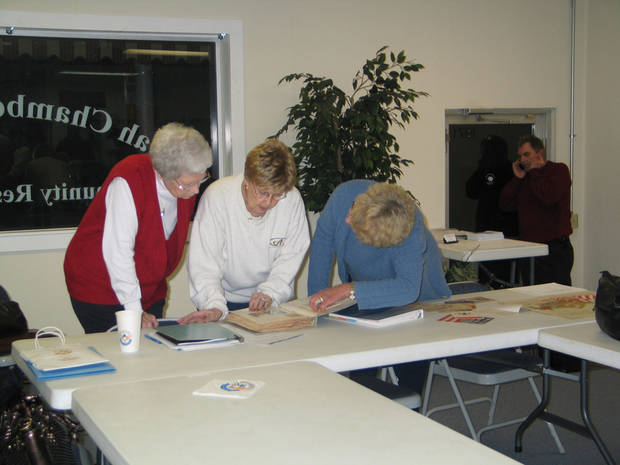 Ruth Shaw, Jeanie Weller, and Betty Batt look at recent acquisitions at the Harrah Historical Society�s Centennial Celebration, November 15<br/><b>Community Photo By:</b> Karen Erbin, Editor<br/><b>Submitted By:</b> Karen, Harrah
