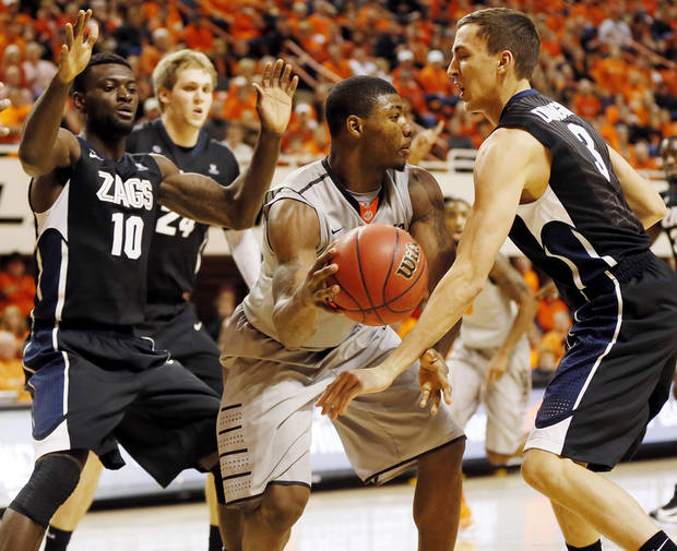 Oklahoma State's Marcus Smart (33) tries to pass away from Gonzaga's Guy Landry Edi (10) and Kyle Dranginis (3) during a men's college basketball game between Oklahoma State University (OSU) and Gonzaga at Gallagher-Iba Arena in Stillwater, Okla., Monday, Dec. 31, 2012. Photo by Nate Billings, The Oklahoman