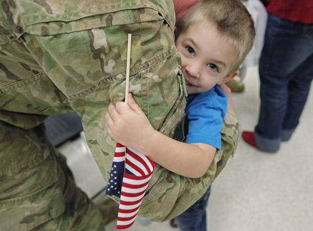 Gunnar Farrar, 3, hugs his dad Sgt. Denton Farrar as Oklahoma National Guardsmen are greeted by family and friends on their return from Afghanistan on Friday, Feb. 17, 2012, in Norman, Okla.   Photo by Steve Sisney, The Oklahoman