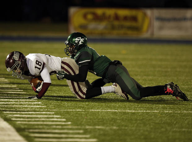 Santa Fe's Dhaniel Bly (13) takes down Memorial's Edmund Pedulla (18) during a high school football game between Edmond Memorial and Edmond Santa Fe at Wantland Stadium in Edmond, Okla., Friday, Oct. 26, 2012.  Photo by Garett Fisbeck, The Oklahoman