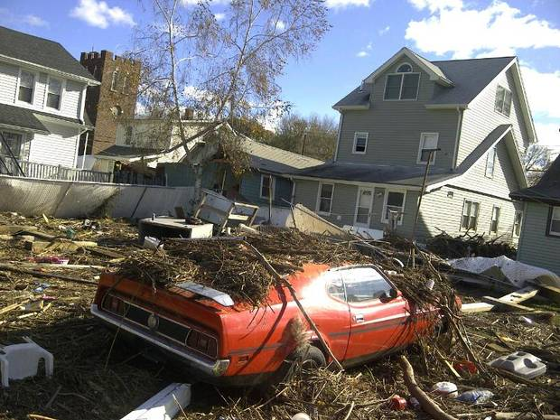A sports car remains covered with debris almost a week after superstorm Sandy passed through the region, Saturday, Nov. 3, 2012 in the New Dorp section of the Staten Island borough of New York.  More New Yorkers awoke Saturday to power being restored for the first time since Superstorm Sandy pummeled the region, but patience wore thin among those in the region who have been without power for most of the week. (AP Photo/Robert Hirsch) ORG XMIT: NYR104