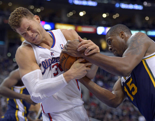 Los Angeles Clippers forward Blake Griffin, left, struggles for the ball with Utah Jazz forward Derrick Favors during the first half of an NBA basketball game, Sunday, Dec. 30, 2012, in Los Angeles. (AP Photo/Mark J. Terrill)