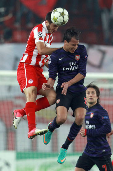 Olympiakos' Kostas Manolas, left, fights for the ball with Arsenal's Marouane Chamakh during their group B Champions League soccer match in the port of Piraeus, near Athens, Tuesday, Dec. 4, 2012. (AP Photo/Thanassis Stavrakis)