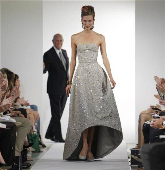 Fashion designer Oscar de la Renta watches as the final model walks the runway during the presentation of his Spring 2013 collection at Fashion Week in New York, Tuesday, Sept. 11, 2012.  (AP Photo/Kathy Willens)
