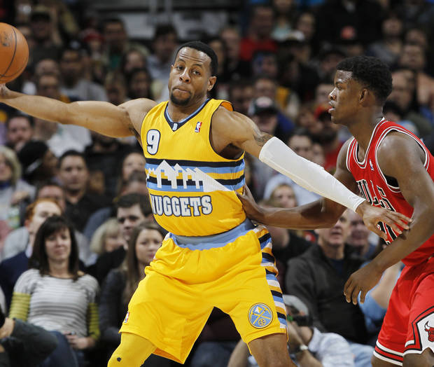 Denver Nuggets guard Andre Iguodala, left, reaches out ot pull in a loose ball as Chicago Bulls guard Jimmy Butler covers in the first quarter of an NBA basketball game in Denver on Thursday, Feb. 7, 2013. (AP Photo/David Zalubowski)