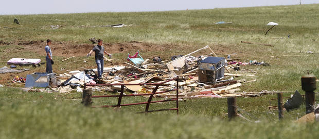 A man and a boy appear overwhelmed on Saturday, June 1, 2013, when they survey damage to this building south of the El Reno Airport after it was blown apart in Friday night's tornado.  Photo  by Jim Beckel, The Oklahoman.