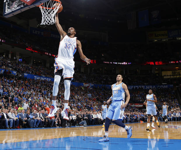 Oklahoma City's Kevin Durant dunks the ball in front of Denver's JaVale McGee during an NBA basketball game between the Oklahoma City Thunder and the Denver Nuggets at Chesapeake Energy Arena in Oklahoma City, Tuesday, March 19, 2013. Photo by Bryan Terry, The Oklahoman
