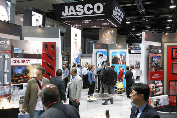 Attendees of the 2013 International CES Show look Tuesday at products offered by Oklahoma City-based Jasco Products in Las Vegas.