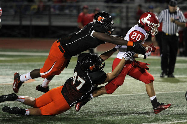 Lawton running back Casey Nadeau is tackled by Norman's Blake Dean and Spencer Jones during the Lawton - Norman High School football game at Harve Collins Field at Norman High School in Norman Friday night. PHOTO BY HUGH SCOTT FOR THE OKLAHOMAN ORG XMIT: KOD