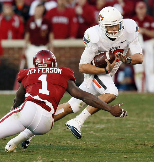 Oklahoma State's Clint Chelf (10) carries the ball against Oklahoma's Tony Jefferson (1) in the third quarter during the Bedlam college football game between the University of Oklahoma Sooners (OU) and the Oklahoma State University Cowboys (OSU) at Gaylord Family-Oklahoma Memorial Stadium in Norman, Okla., Saturday, Nov. 24, 2012. OU won, 51-48 in overtime. Photo by Nate Billings , The Oklahoman