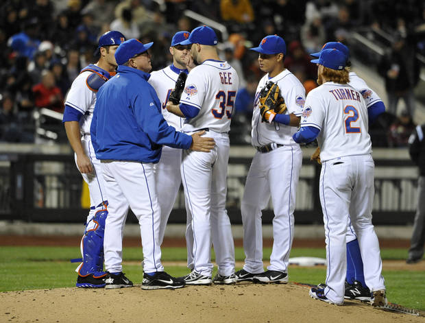 New York Mets pitching coach Dan Warthen (blue jacket) has a meeting on the mound with starting pitcher Dillon Gee (35) after the Atlanta Braves scored three runs in the fifth inning of the second baseball game at Citi Field, Saturday, May 25, 2013, in New York. (AP Photo/Kathy Kmonicek)