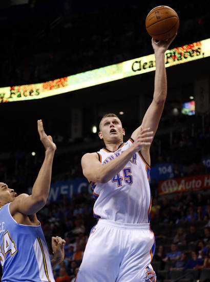 Oklahoma City's Cole Aldrich (45) shoots over Denver's JaVale McGee (34) during the NBA preseason basketball game between the Oklahoma City Thunder and the Denver Nuggets at the Chesapeake Energy Arena, Sunday, Oct. 21, 2012. Photo by Sarah Phipps, The Oklahoman